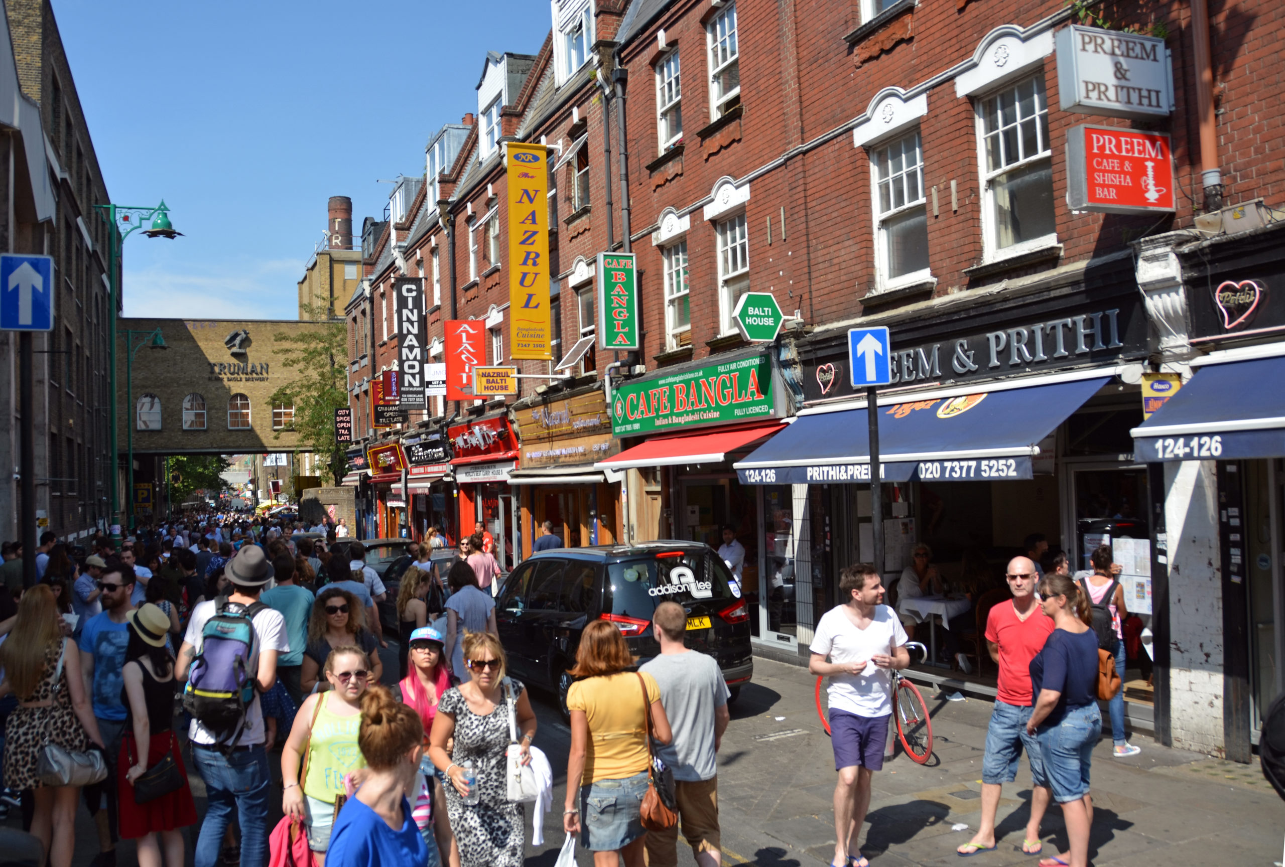 Tourists walking through Brick Lane, Tower Hamlets on a busy summers afternoon on July 21, 2013 in London