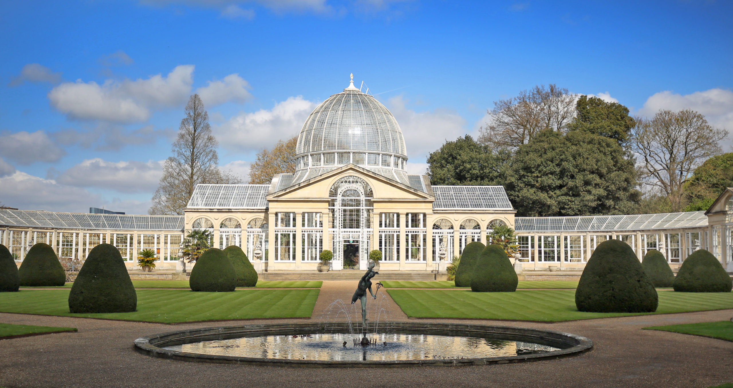 Syon Park in Brentford, West London, England. A large glass house against a pale blue sky in a landscaped garden. London Tourist Attraction.