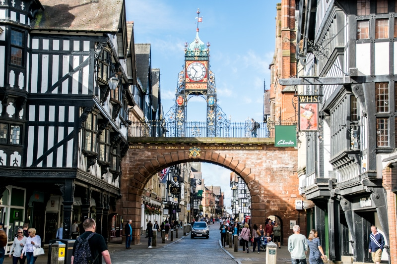 Locals and tourists walking under the city gate of the old town Chester including view of Eastgate Clock.