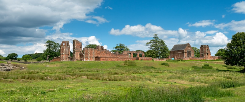Panoramic view of the ruins of Bradgate House Within Bradgate park surrounded by green fields and trees on a summer day with blue skies and some clouds.