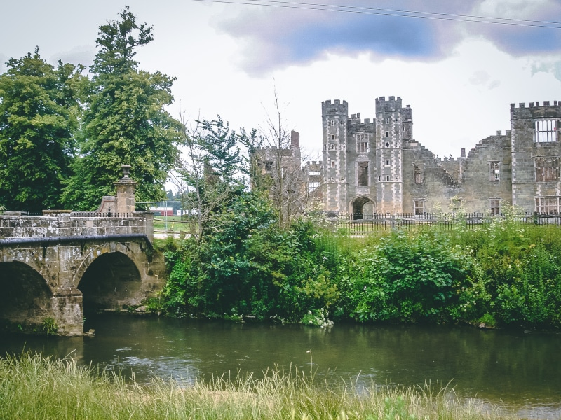 The ruins of the great Tudor house of Cowdray in Midhurst and stone bridge crossing the River Rother