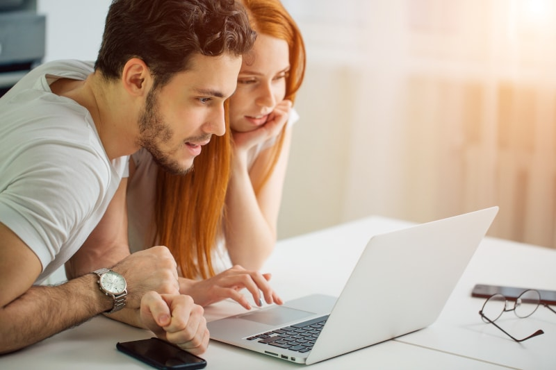 Two people looking excitedly at a laptop in their home doing some research with some sunshine coming through the window behind them.