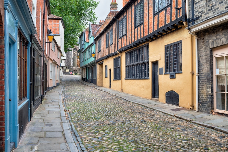 View of a small, old Tudor cobbled street with original housing of yellow orange and blue painted exterior walls.