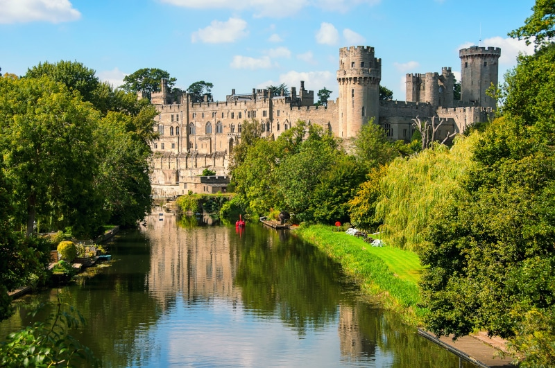 View of Warwick Castle reflecting in the river Avon surrounded by thick green trees on a sunny summers day with some clouds.