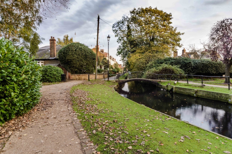 A popular canal crossing to a park in the North London borough of Enfield on an autumn cloudy day with many leaves on the ground.